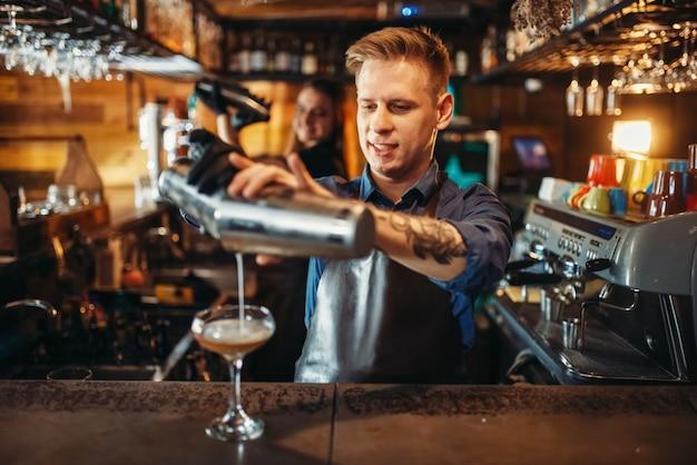 Mężczyzna barman nalewa napój z shakera