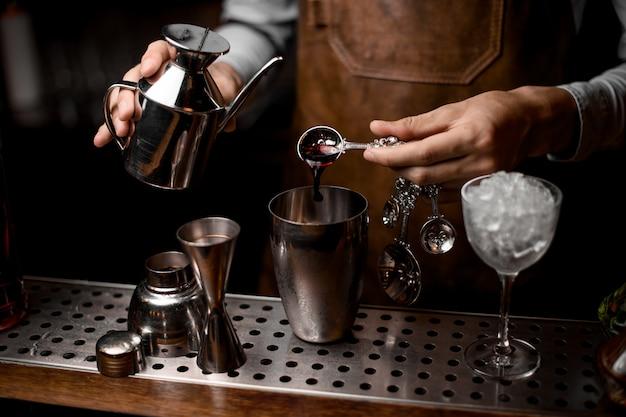 Mężczyzna barman nalewający esencję z łyżki do stalowej wytrząsarki