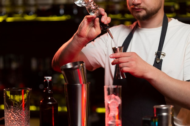 Mężczyzna barman robi koktajl z shakerem