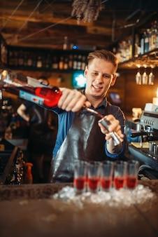 Mężczyzna barman w fartuchu przygotowuje koktajl alkoholowy