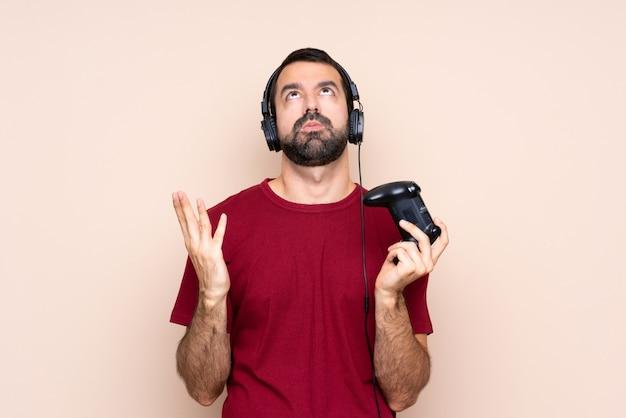 Mężczyzna bawi się kontrolerem gier wideo na izolowanej ścianie sfrustrowany złą sytuacją