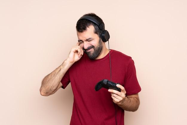 Mężczyzna bawi się kontrolerem gier wideo na izolowanych ścianach sfrustrowanych i zakrywających uszy