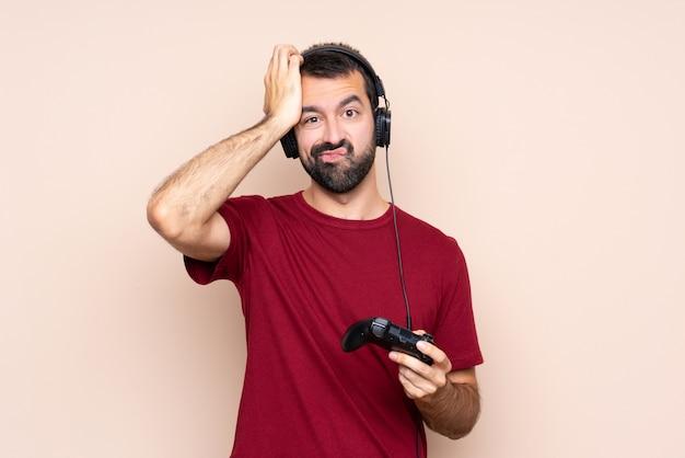 Mężczyzna bawi się kontrolerem gier wideo z wyrazem frustracji i braku zrozumienia