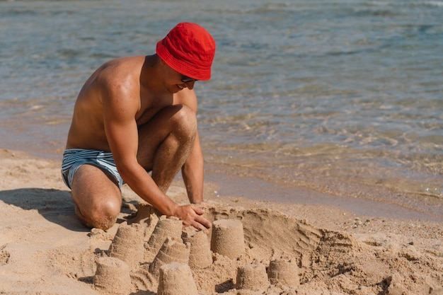 Mężczyzna bawi się piaskiem na plaży