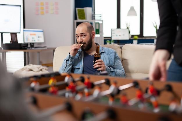 Mężczyzna bawi się pijąc piwo po pracy w biurze