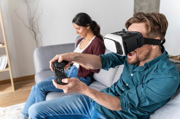 Mężczyzna bawi się w domu na kanapie z zestawem słuchawkowym wirtualnej rzeczywistości, grając w gry wideo