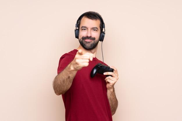 Mężczyzna bawiący się kontrolerem gier wskazuje na ciebie palcem z pewnym siebie wyrazem twarzy