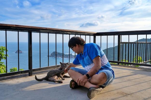Mężczyzna bawiący się z kotem na tarasie z widokiem na morze
