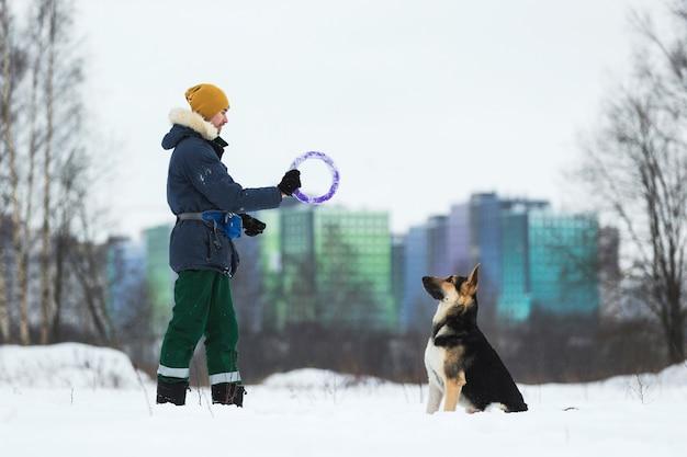 Mężczyzna bawiący się z owczarkiem niemieckim w parku zimą