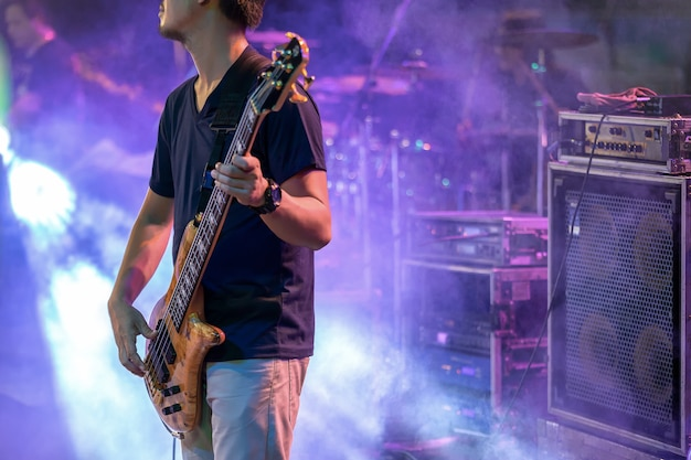 Mężczyzna bawić się elektryczną basową gitarę na scenie dla tła