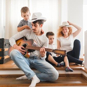 Mężczyzna bawić się gitarę dla jego rodziny w domu