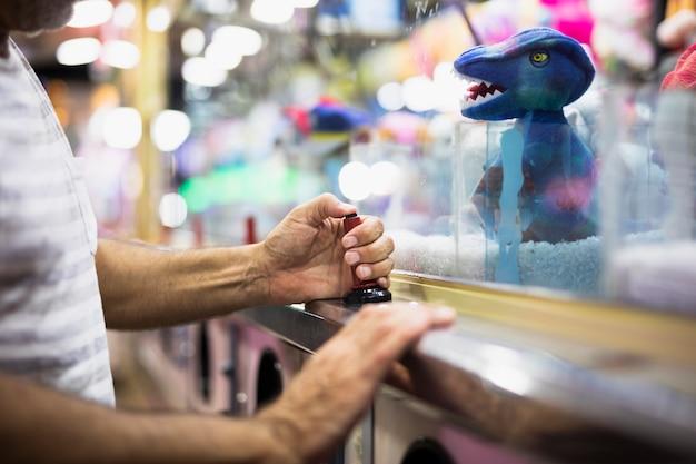 Mężczyzna bawić się holowniczą pazur maszynę