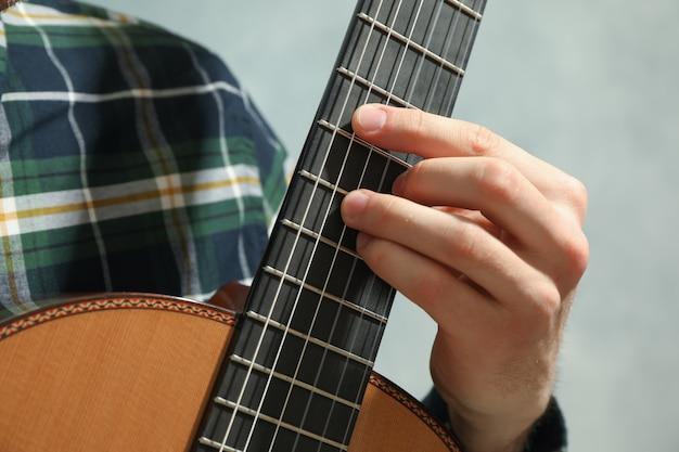 Mężczyzna bawić się na klasycznej gitarze, zbliżenie