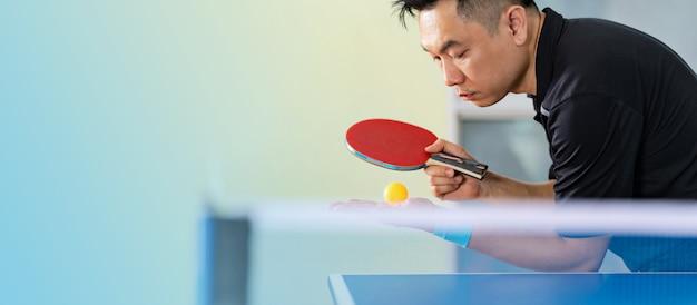 Mężczyzna bawić się stołowego tenisa z kantem i piłką w hali sportowa
