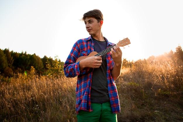 Mężczyzna bawić się ukulele i patrzeje daleko od