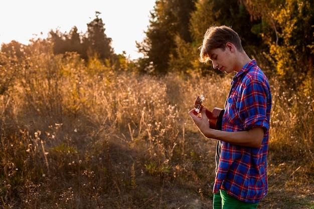Mężczyzna bawić się ukulele środka strzał