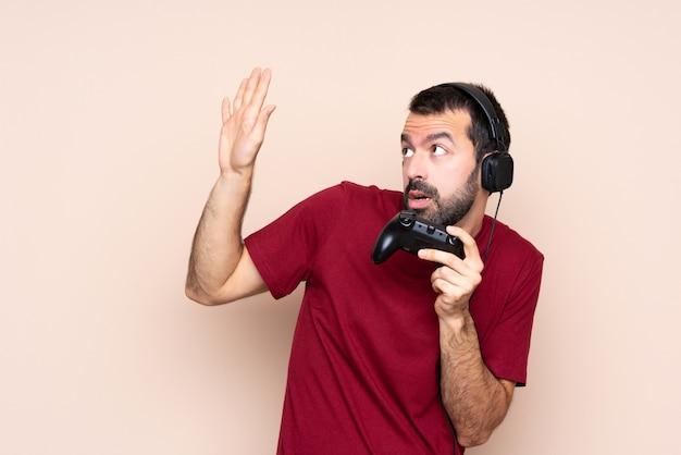 Mężczyzna bawić się z kontrolerem gier wideo nad odosobnioną ścianą nerwową i przestraszoną