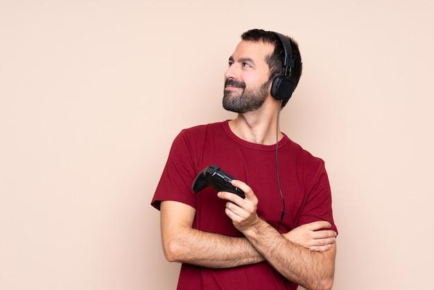 Mężczyzna bawić się z kontrolerem gier wideo nad odosobnioną ścianą szczęśliwą i uśmiechniętą