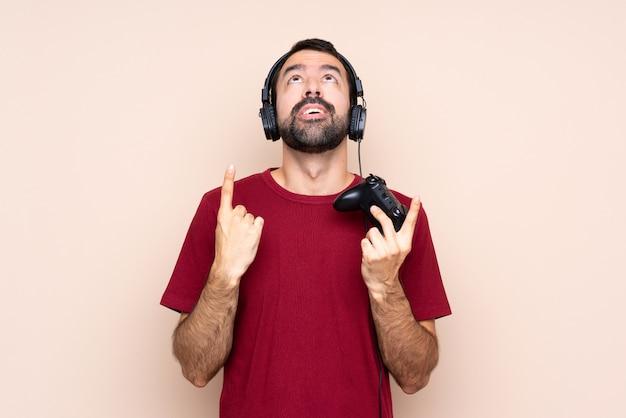 Mężczyzna bawić się z kontrolerem gier wideo nad odosobnioną ścianą zaskakującą i wskazuje up