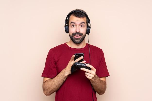 Mężczyzna bawić się z kontrolerem gier wideo nad odosobnioną ścianą zaskakującą i wysyła wiadomość