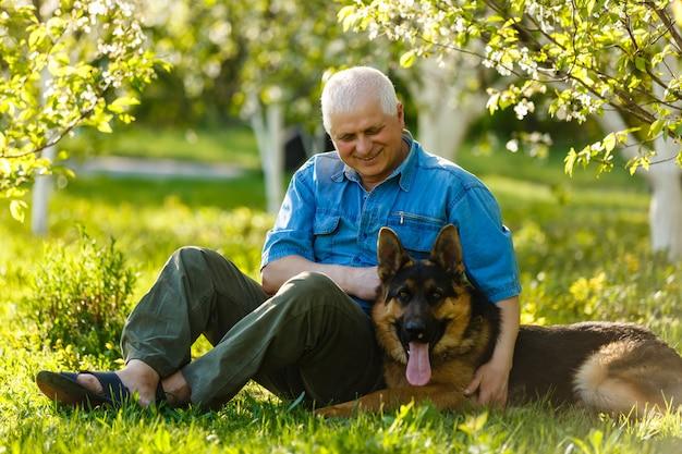 Mężczyzna bawić się z psem owczarek niemiecki w parku