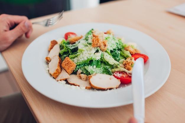 Mężczyzna będzie jadł sałatkę cezar w restauracji. posiadanie smacznej zdrowej żywności. ładna prezentacja