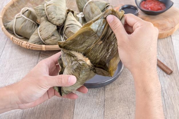 Mężczyzna będzie jadł zongzi lub knedle ryżowe na festiwalu dragon boat, tradycyjnej kuchni azjatyckiej