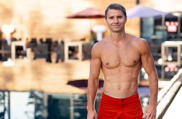 Mężczyzna bez koszuli na basenie z miejscem na kopię