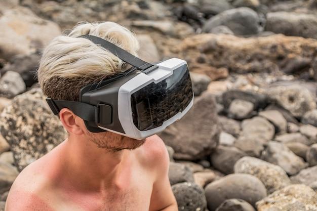 Mężczyzna bez koszuli siedzi na skałach, za pomocą zestawu słuchawkowego wirtualnej rzeczywistości.