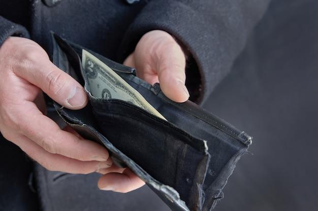 Mężczyzna bez twarzy otworzył portfel z ostatnim rachunkiem. kryzys. skopiuj miejsce