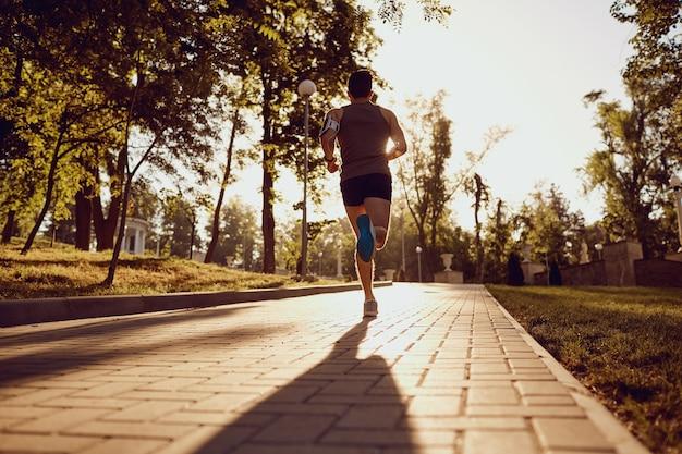 Mężczyzna biegacz biegnie drogą w parku o zachodzie słońca.