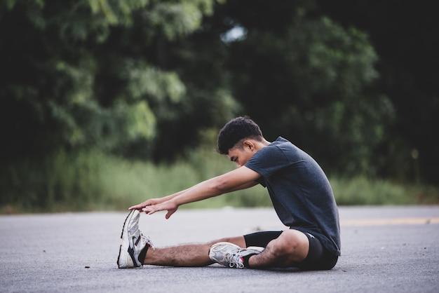 Mężczyzna biegacz robi ćwiczenia rozciągające, przygotowując się do treningu