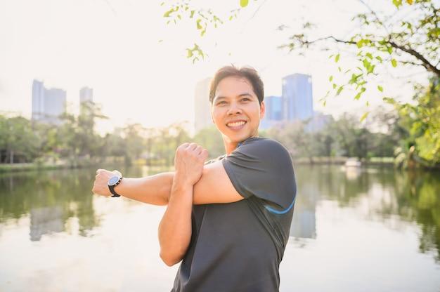 Mężczyzna biegacz robi ćwiczenia rozciągające ramię, rozgrzewka brfore bieganie w parku