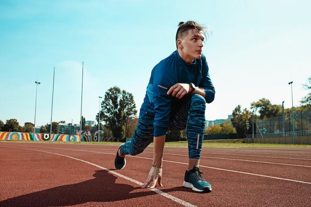 Mężczyzna biegacz rozciąganie nogi przygotowuje się do uruchomienia treningu na torach stadionu robi rozgrzewkę