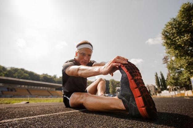 Mężczyzna biegacz rozciąganie przed treningiem.