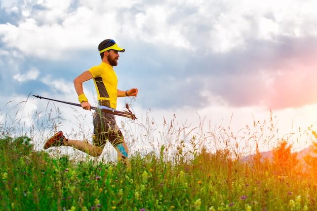 Mężczyzna biegacz z rakietami w ręku w dół na łąkach
