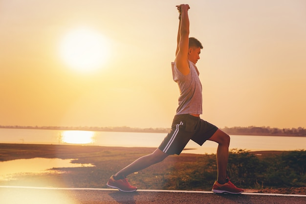 Mężczyzna biegaczy atlety worming up dla plenerowej praktyki z zmierzchu tłem