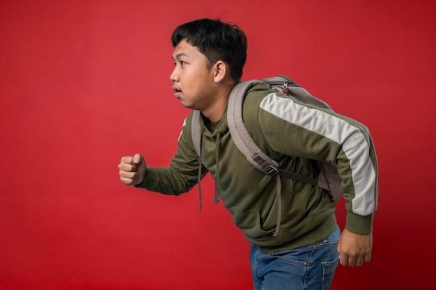 Mężczyzna biegający w plecaku późno do koncepcji szkoły na białym tle na czerwonym tle