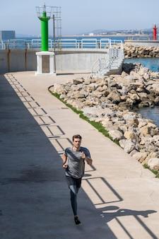 Mężczyzna biegnący przez port z czystym niebem, nosi odzież sportową