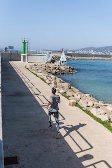Mężczyzna biegnący w kierunku latarni morskiej z czystym niebem, nosi odzież sportową