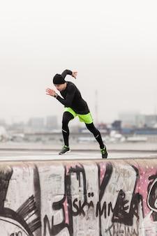Mężczyzna biegnie na dachu w deszczowy dzień