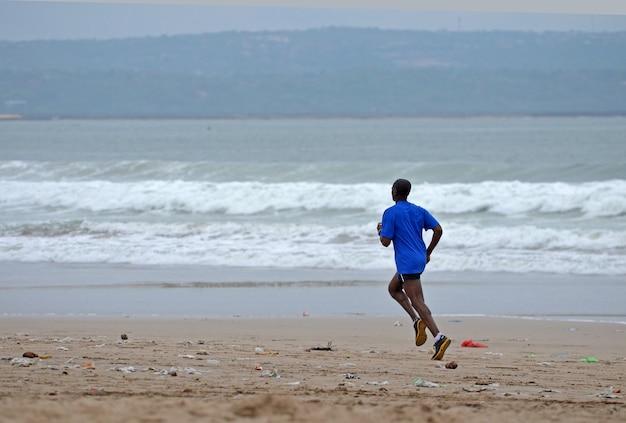 Mężczyzna biegnie po brudnej, piaszczystej plaży po burzy.