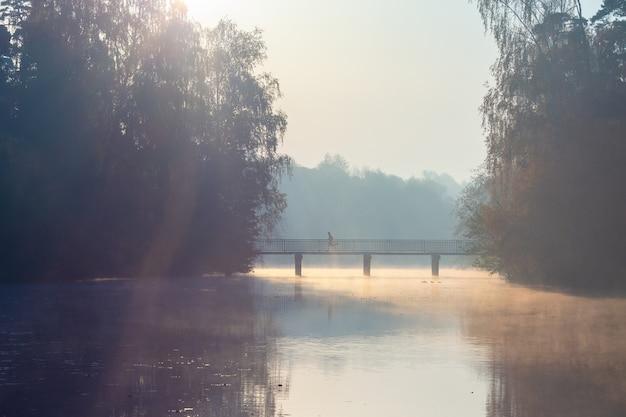 Mężczyzna biegnie przez most o wschodzie słońca.