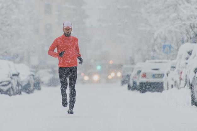 Mężczyzna biegnie ulicą w centrum zaśnieżonego miasta