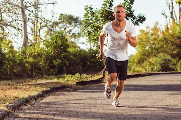 Mężczyzna biegnie w parku.