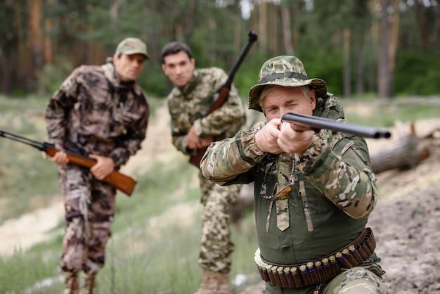 Mężczyzna bierze cel podekscytowani myśliwi oglądający strzał.