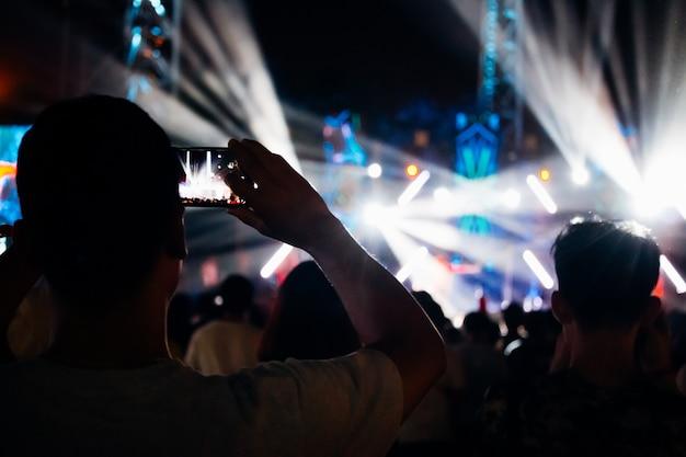 Mężczyzna bierze fotografię z telefonem przy muzycznym wydarzeniem