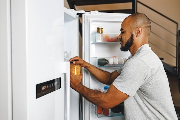 Mężczyzna bierze jedzenie z lodówki w swoim domu