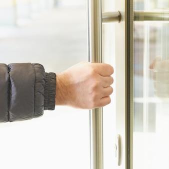 Mężczyzna bierze klamkę za rękę i otwiera drzwi.