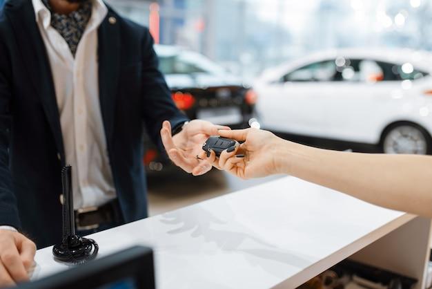 Mężczyzna bierze klucz od nowego samochodu w salonie samochodowym. klient i sprzedawczyni w salonie samochodowym, mężczyzna kupujący transport, firma dealera samochodowego